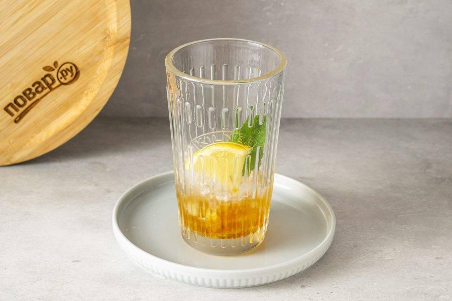 Добавьте в стакан пару долек лимона и листиков мяты.