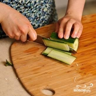 7. Приготовьте острый нож и нарежьте огурец на тонкие пластинки вдоль.