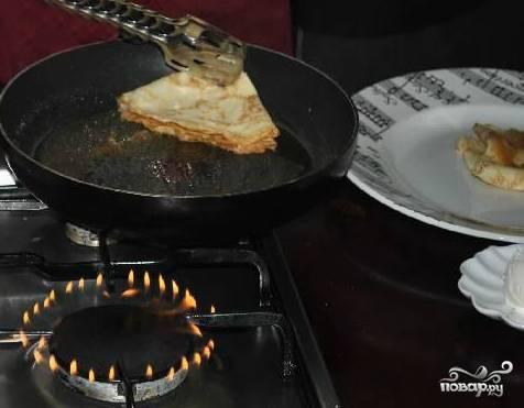 Готовые блинчики складываем вдвое треугольничком. Берем щипчики или нечто подобное и обмакиваем каждый блинчик в растопленный сахар одной из сторон. Кладем блинчик на тарелку сухой стороной.