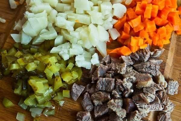 Нарежьте кубиками мясо, огурцы, картофель и морковь. Смешайте их.