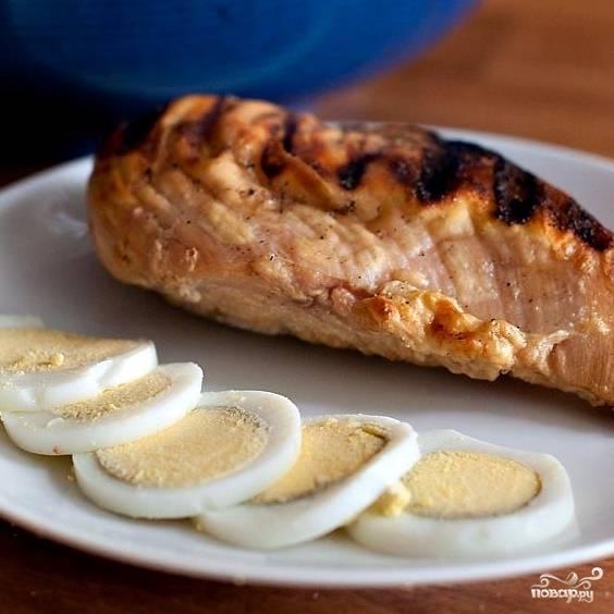 Кусок куриного филе целиком необходимо обжарить на сковороде-гриль, ну или на обычной сковороде. Примерно по 3-4 минуты с каждой стороны, до образования уверенной корочки. Внутри мясо должно оставаться сочным. Яйца отвариваем вкрутую и нарезаем слайсами.