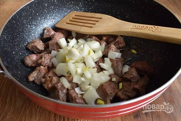 Лук и морковь очистите. Лук нашинкуйте, добавьте к мясу, слегка обжарьте.