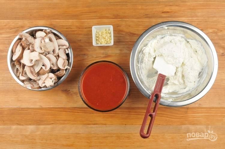 2. Чеснок мелко нарубите. Соус смешайте с 1/3 стакана воды. Промытые шампиньоны нарежьте слайсами. К рикотте мелко натрите половину моцареллы, также добавьте соль и перец. Сырную смесь перемешайте.