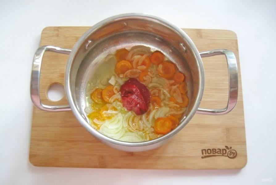 Налейте подсолнечное масло и поджарьте в течение 7-8 минут, периодически перемешивая. Добавьте томатную пасту.