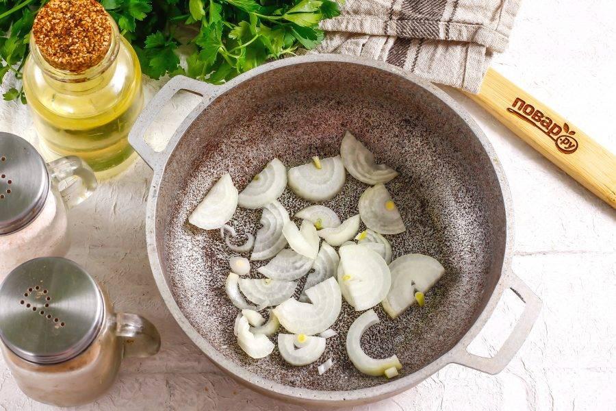 Очистите и промойте репчатый лук, нарежьте полукольцами. Влейте в казан или емкость с антипригарным дном растительное масло, выложите луковую нарезку и обжарьте около 2-3 минут.