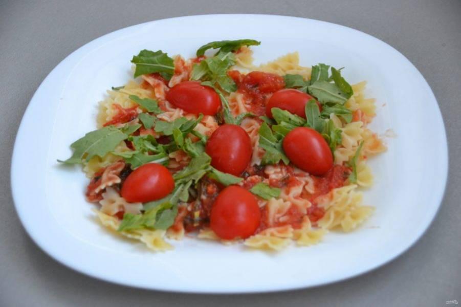 Добавьте зелень рукколы и помидорки черри, нарезанные половинками.