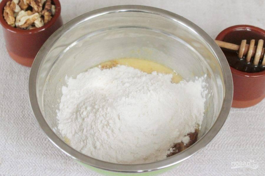 Добавляем в миску стакан муки и гашенную соду. Перемешиваем. Оставшуюся муку подсыпаем порциями.