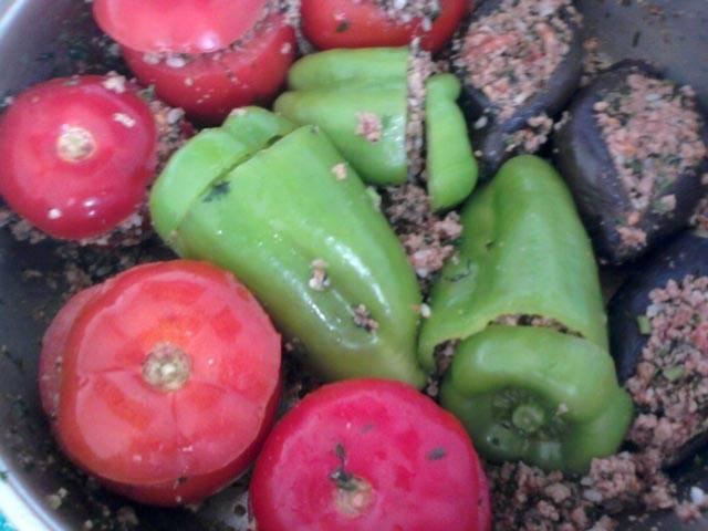 Наполняем баклажаны и другие овощи начинкой. Выкладываем долму в глубокую жаропрочную емкость. Вливаем пол стакана воды, добавляем один перетертый на терке помидор. Варим 35-40 минут на среднем огне.