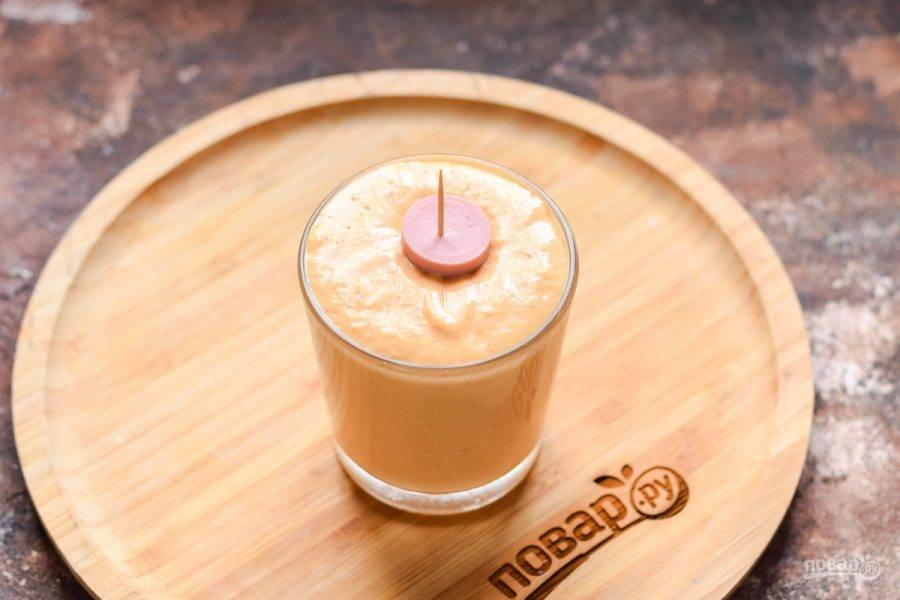 Приготовленный кляр перелейте в стакан или чашку, окуните сосиску, чтобы она вся была покрыта нашим кляром.