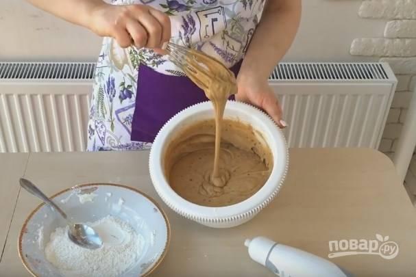 4. Добавьте несколько ложек просеянной муки, перемешайте. Затем всыпьте разрыхлитель и начните взбивать миксером, продолжая постепенно добавлять остаток муки. Тесто должно быть по консистенции, как на бисквит, не гуще.