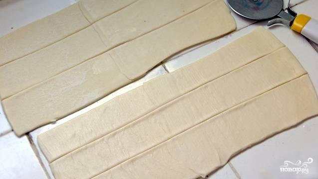 Раскатываем слоеное тесто потоньше, после чего нарезаем его на полоски шириной 2 см.