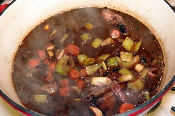 7. Добавить к овощам томатную пасту, соль и перец по вкусу. Влить бульон и немного маринада. Довести до кипения на огне.