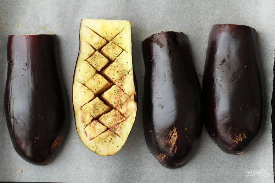 2.Выложите баклажаны на противень с пергаментом, смажьте баклажаны оливковым маслом, переверните срезом вниз.