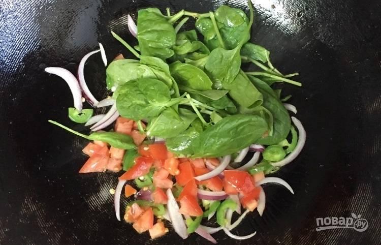 2.Вымойте шпинат, нарежьте кусочками помидоры. Выложите овощи к остальным в сковороде.