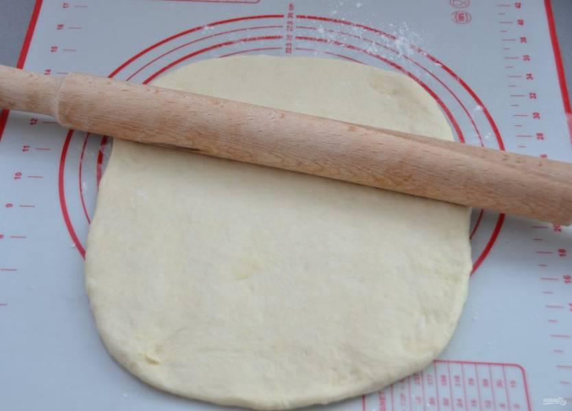 Подошедшее тесто выложите на рабочую поверхность стола, слегка припыленную мукой, раскатайте в пласт.