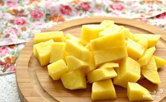 Картофель помойте и почистите. Нарежьте его средними кубиками и вкиньте в кастрюлю следом за перловкой.