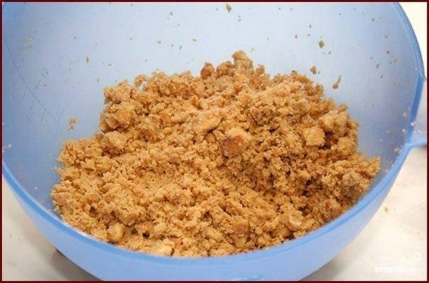 В измельченное печенье добавляем мелко нарубленное холодное сливочное масло. Все хорошенько перемешиваем.