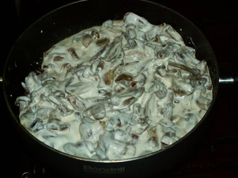 5. Затем - добавим нарезанные тонкими пластиночками шампиньоны и заливаем сметаной. Солим, перчим, тушим до готовности.