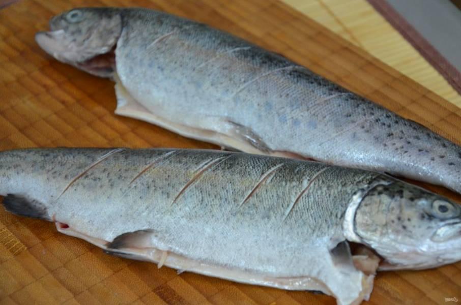 2. Делаем небольшие надрезы на поверхности рыбы. Это нужно для того, чтобы во время запекания шкура не пузырилась и не рвалась, а также для того, чтобы маринад лучше пропитал тушку.