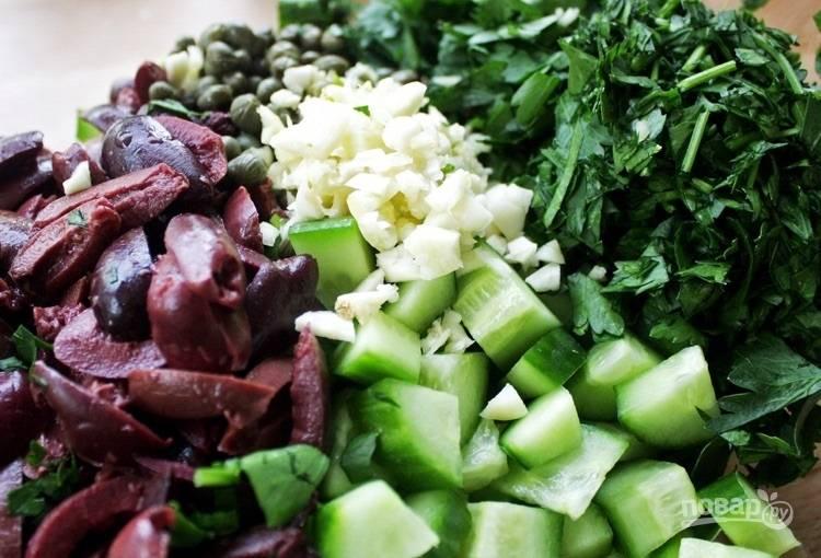 4.Нарежьте оливки, измельчите чеснок. Выложите в миску оливки, чеснок, петрушку, каперсы, огурцы, добавьте сок и цедру лимона.