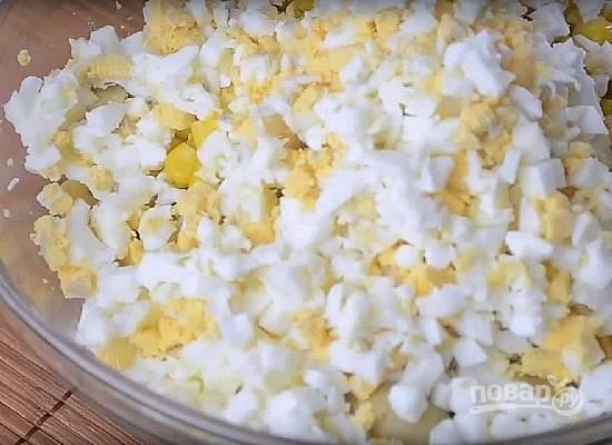 Добавляем нарезанные кубиками вареные яйца.