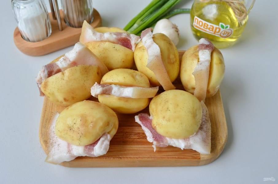 3. Картофель разрежьте на половинки, не дорезая до конца, можно сделать клинообразный разрез, чтобы вставить кусочек сала. Посолите и поперчите картофель внутри и снаружи. Смажьте растительным маслом, чтобы образовалась вкусная корочка.