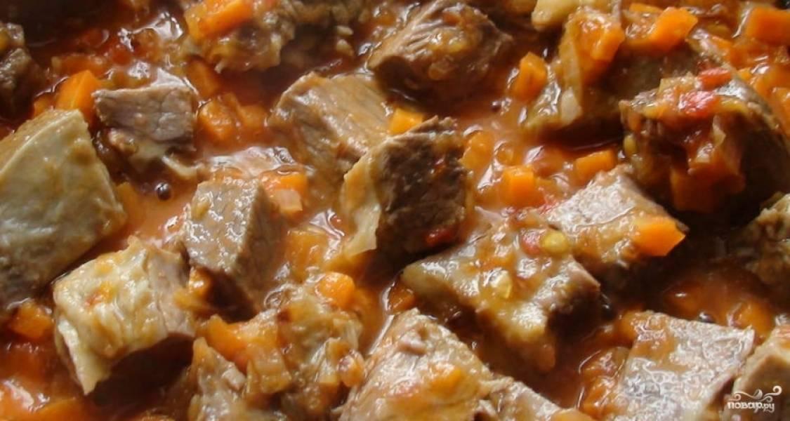 Помидор помойте. Натрите его на тёрке без кожицы. Добавьте томатную кашицу в сковороду к овощам. Готовьте всё вместе на сильном огне в течение минуты. Потом добавьте мясо. Тушите подливу ещё 2 минуты на среднем огне.