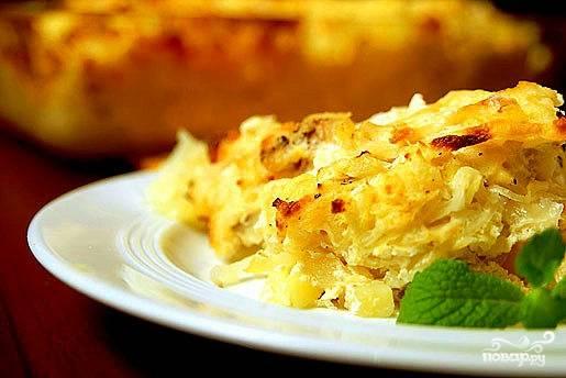 Смешать тертый картофель с 2/3 тертого сыра, измельченным чесноком и яично-сметанной смесью. Выложить в форму, сверху посыпать остатками сыра. Накрыть фольгой и запекать при 180С полчаса. Затем фольгу открыть и готовить до тех пор, пока сыр не расплавится и образует золотистую румяную корочку. Подавать прямо в форме или нарезанной, как пирог, на порционных тарелках.