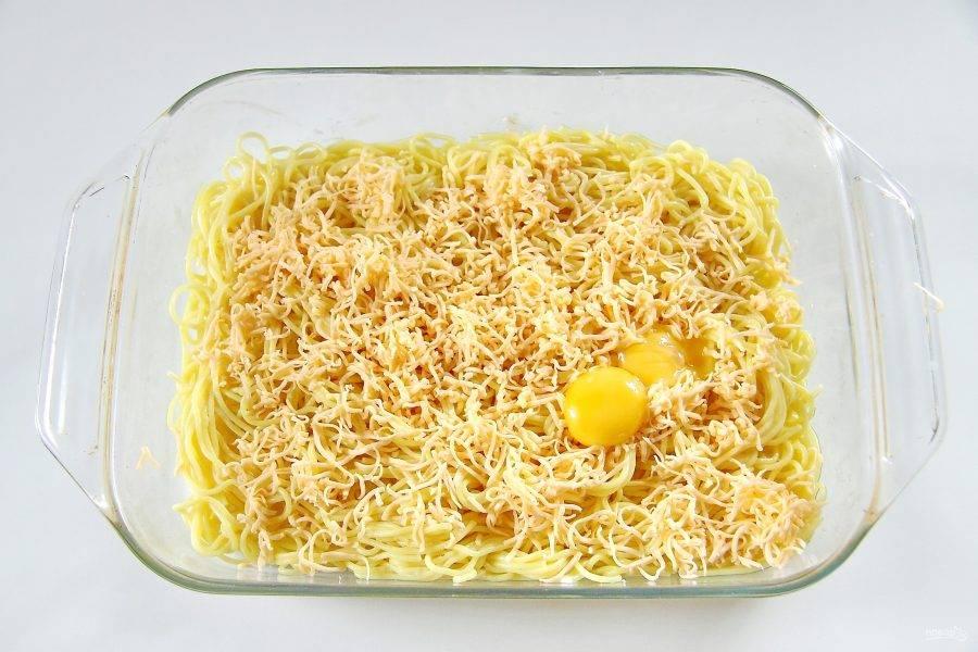 Перемешайте спагетти с маслом и добавьте мелко натертый сыр (немного оставьте для начинки) и яичные желтки.