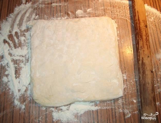 Раскатать в прямоугольник на листе бумаги( так будет удобнее перенести пирог на противень) слоеное тесто. Толщина готового листа должна быть около 1 сантиметра.