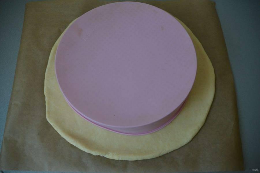 Раскатайте тесто в пласт на пергаменте для выпечки, выложите сверху форму для выпечки, обозначьте габариты.
