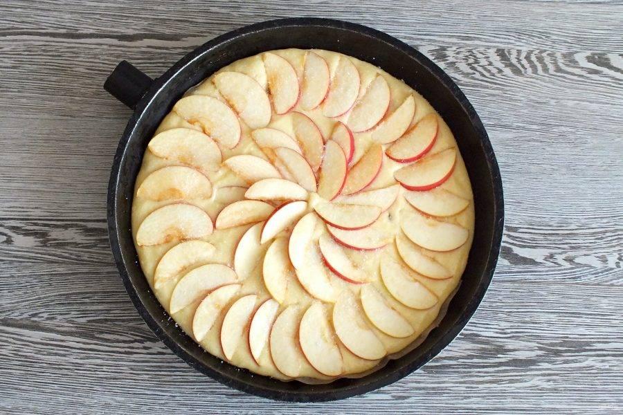 Форму для выпечки смажьте сливочным маслом или застелите бумагой для выпечки. Перелейте тесто, сверху разложите яблоки. Посыпьте сахаром. Поставьте выпекаться пирог в разогретую до 180 градусов духовку на 25-30 минут.