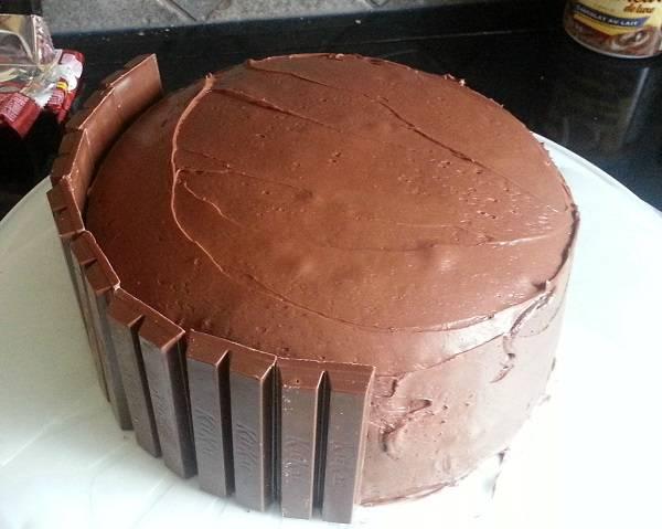 """2. Дальше начинается самое интересное. Бока тортика нужно обложить батончиками. В рецепте приготовления торта для мамы можно использовать не только """"Кит-Кат"""", но они подходят очень хорошо."""