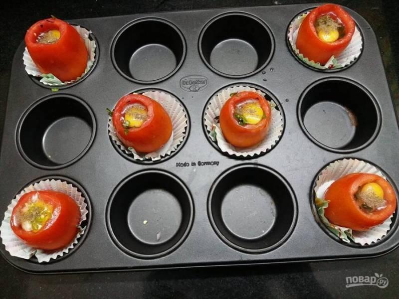 3. Поставьте помидоры в формочку для кексов. Вбейте яйца, приправьте измельченным чили, луком, перцем и солью по вкусу. Запекайте в духовке в течение 20 минут.