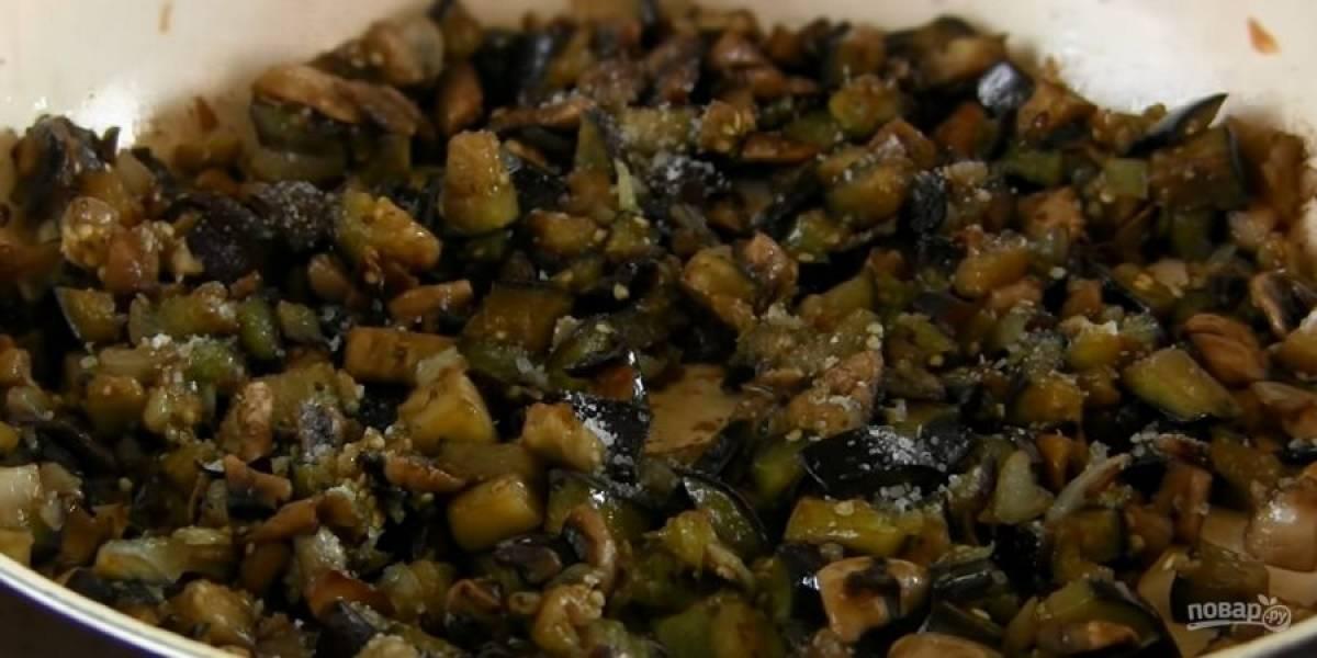 2. На растительном масле обжарьте до легкого золотистого цвета лук. Добавьте к нему грибы и баклажаны, готовьте на среднем огне в течение 10 минут, периодически помешивая.