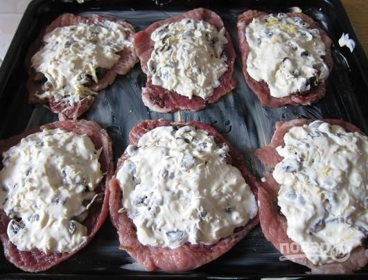 Дальше выкладываем сырную смесь на грибы и отправляем противень в разогретую до 180 градусов духовку на 40 минут.