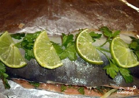 4.Теперь второй половинкой рыбного филе закрываем начинку. Сверху выложить на рыбу веточки петрушки и кольца лимона. Все завернуть в фольгу и запекать рыбу в духовке при 180 градусах около часа. За несколько минут до готовности откройте фольгу, чтобы рыба сверху немного запеклась. Выложить рыбу на блюдо, украсить его зеленью и лимоном. Все. Приятного аппетита!