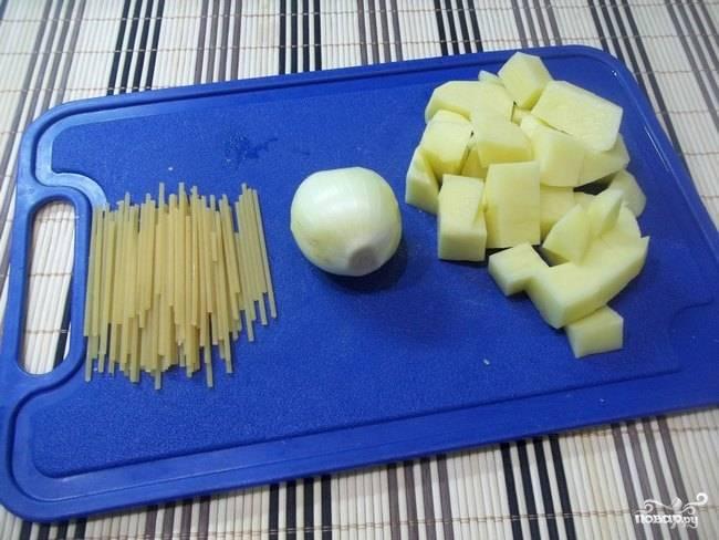 2. Первым делом очистите картофель и нарежьте небольшими кубиками. Луковицу в данном случае для бульона можно использовать целиком (но при желании вы можете измельчить ее кубиками и обжарить на сковороде до прозрачности). Спагетти поломайте.