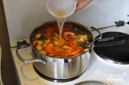 Пробуем суп, если надо — добавляем соль. Затем добавляем креветки, нарезанный на кусочки перец чили и сок лайма.
