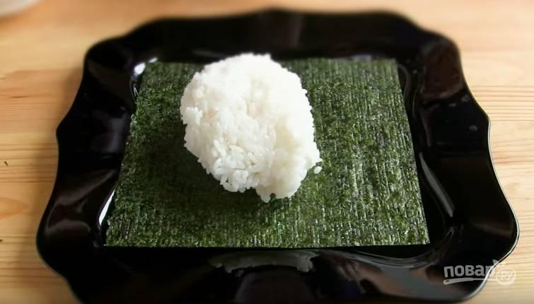 6. Теперь соберите торт. Лист нори положите шероховатой стороной вверх и распределите рис тонким слоем мокрыми руками.