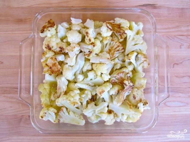 5. Выберите цветную капусту из духовки и поместите в посуду для запекания. Сбавьте температуру духовки до 190 градусов.