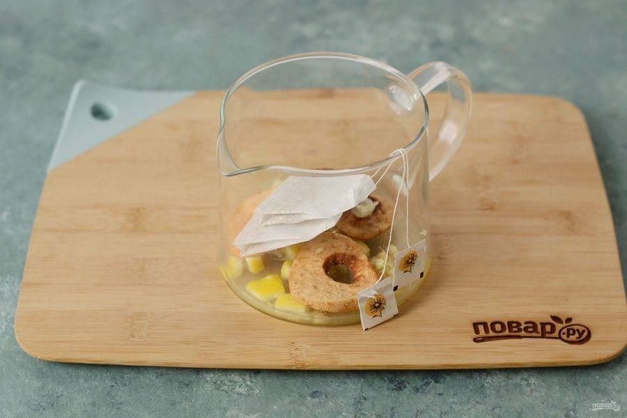 Выложите в заварочный чайник лимон, имбирь и сушеные яблоки. Добавьте сушеную ромашку.