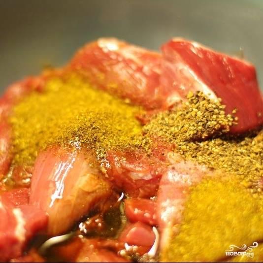 Баранину нарежьте на куски, подходящие для приготовления шашлыка (все плевки и сухожилия обязательно удалите). Положите нарезанное мясо в миску, добавьте специи, масло и уксус. Перемешайте.