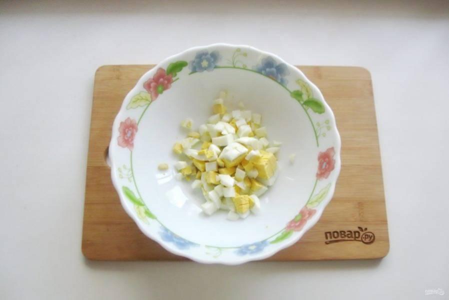 Яйца сварите вкрутую, охладите и очистите. После мелко нарежьте и выложите в салатник.