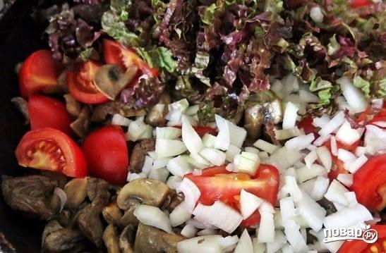 К обжаренным ингредиентам добавьте очищенный и нашинкованный на мелкие кубики репчатый лучок. Листья салата вымойте и порвите руками. Отправьте их к остальным ингредиентам.
