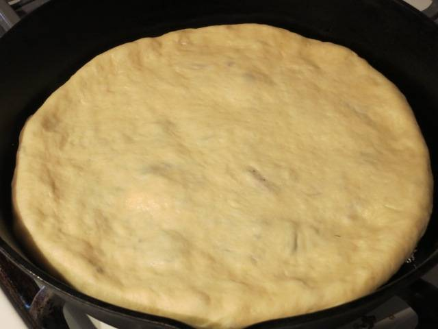 Соедините тесто сверху начинки в виде узелка и расплющите рукой. Швом вниз положите её в круглую смазанную форму и аккуратно разомните и растяните её по всей поверхности формы. В центре пирога сделайте небольшое отверстие для выхода пара. Разогрейте духовку до 250 градусов и выпеките в течение 15 минут. Готовые пироги смажьте растопленным сливочным маслом. На стол подавайте в теплом виде.