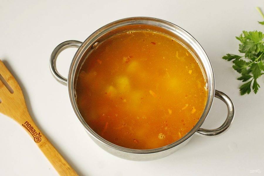 Добавьте в бульон картофель, соль по вкусу и овощную зажарку. Поставьте на плиту и варите до полной готовности картофеля.