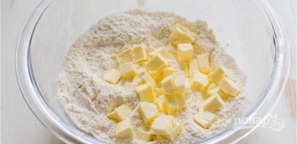 1. В глубокую емкость просейте муку, разрыхлитель и 1/4 стакана сахара. Добавьте к сухой смеси 100 грамм сливочного масла.