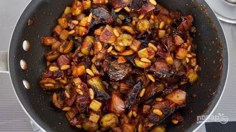 6.Добавьте в сковороду изюм, кедровые орехи, баклажаны, готовьте до испарения жидкости и выключите огонь. Остудите и отправьте блюдо в холодильник.