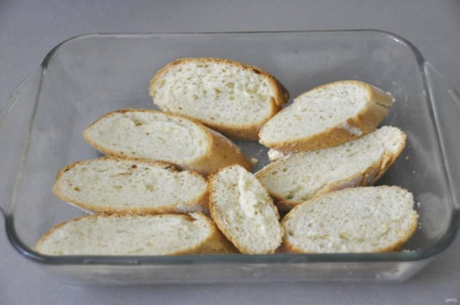 Смажьте форму для запекания сливочным или растительным маслом, дно выложите кусочками багета.
